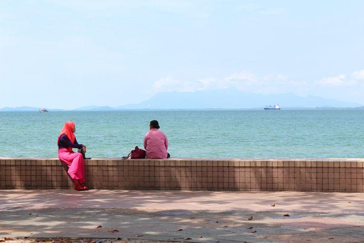 マレーシア・ジョージタウンの海辺で語らう女性たち