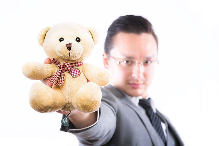 クマのぬいぐるみを持つ男性