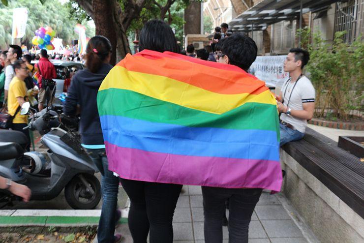 台灣同志遊行(台湾LGBTプライド)2015のパレードでレインボーフラッグを羽織るカップル