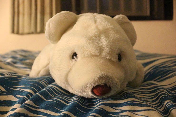 ベッドの上でくつろぐシロクマのぬいぐるみ