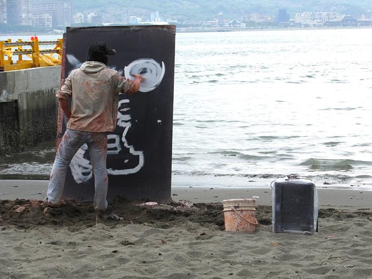 台北・淡水の川辺で絵を描くアーティスト