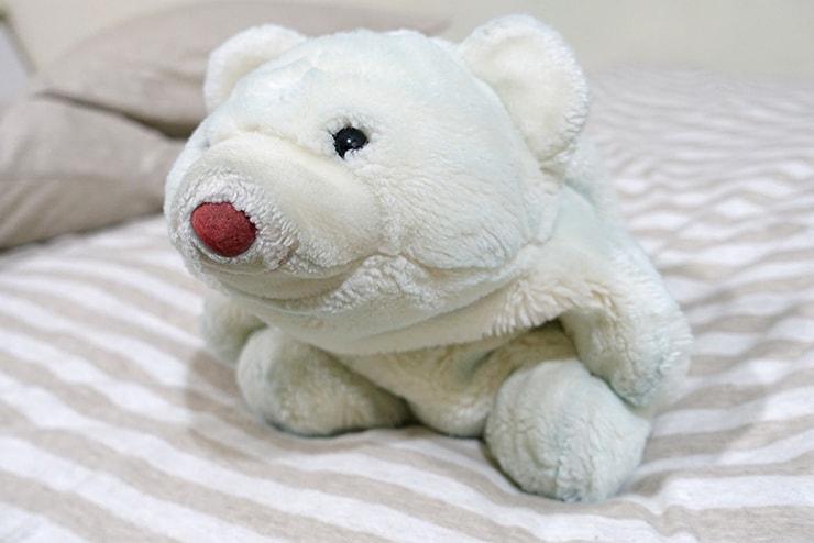 ベッドにちょこんと座るシロクマのぬいぐるみ