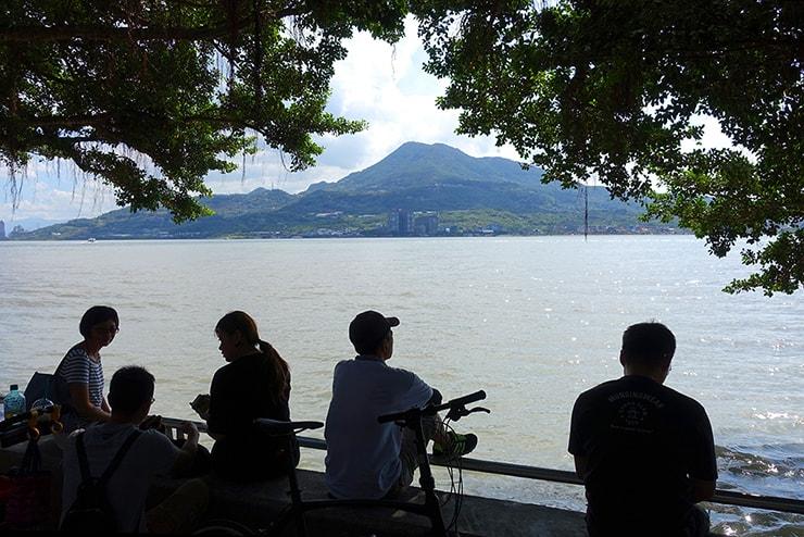 台北・淡水の川辺から対岸の八里を眺める人々