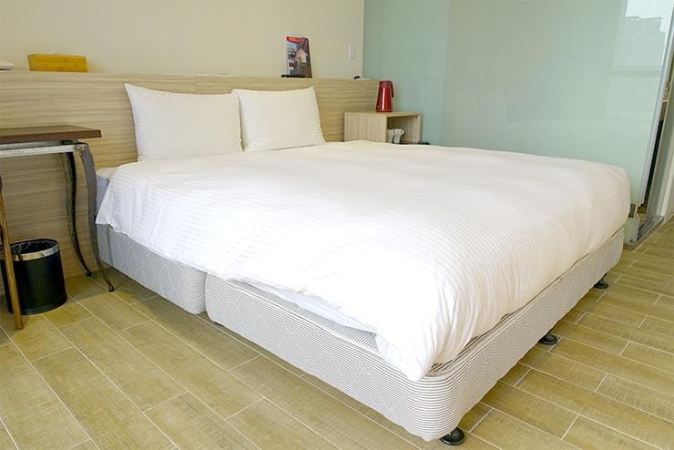 高雄・鹽埕埔の海が見えるロケーション最高のLGBTフレンドリーホテル「塩旅社 Hotel Yam」街景環保雙人房(シティビューダブルルーム)のベッド