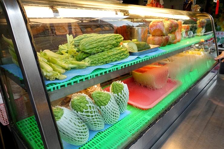 台北・遼寧街夜市「祥好喝現打果汁專賣店」のカウンターに並ぶ果物と野菜たち