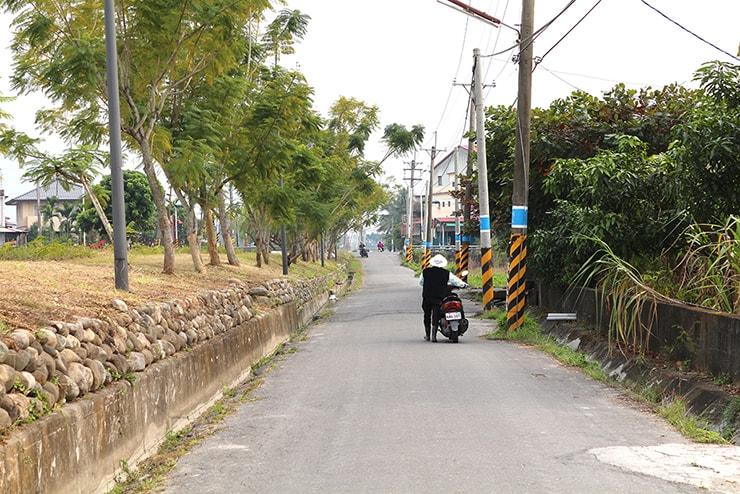 高雄・美濃の道路でスクーターを押して歩くおばさん
