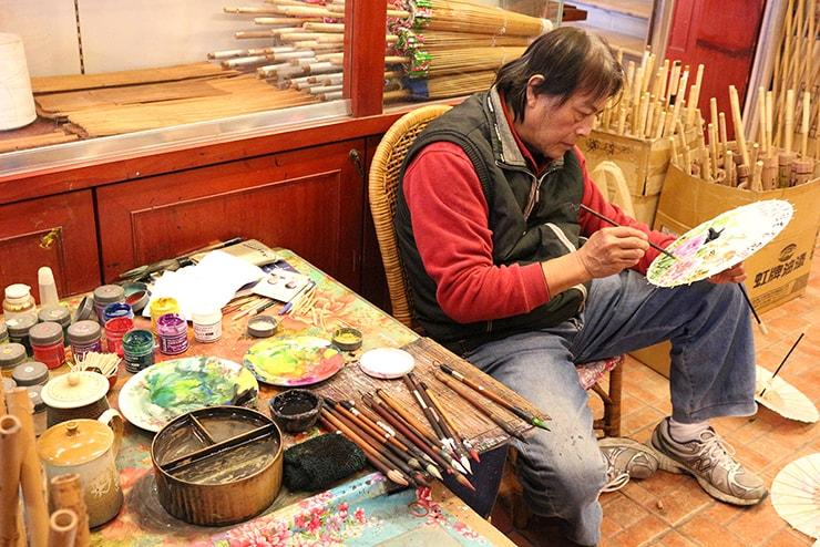高雄・美濃の人気観光スポット「原鄉緣紙傘文化村」で傘の色付けをする職人さん