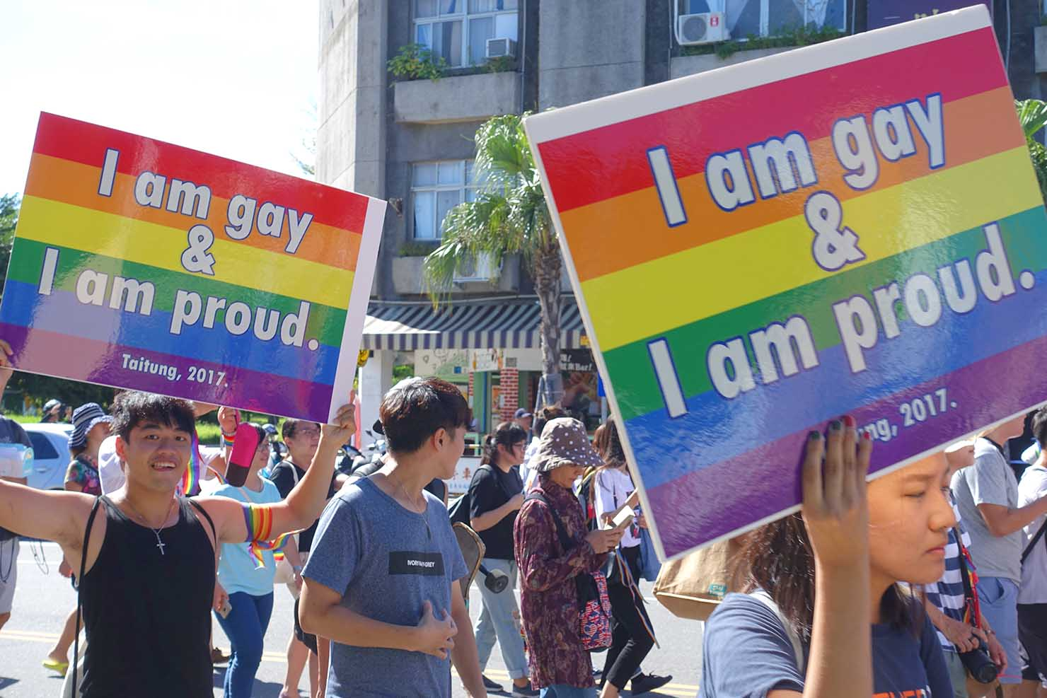 台湾東部のLGBTプライド「花東彩虹嘉年華」でレインボーカラーのプラカードを掲げる参加者たち
