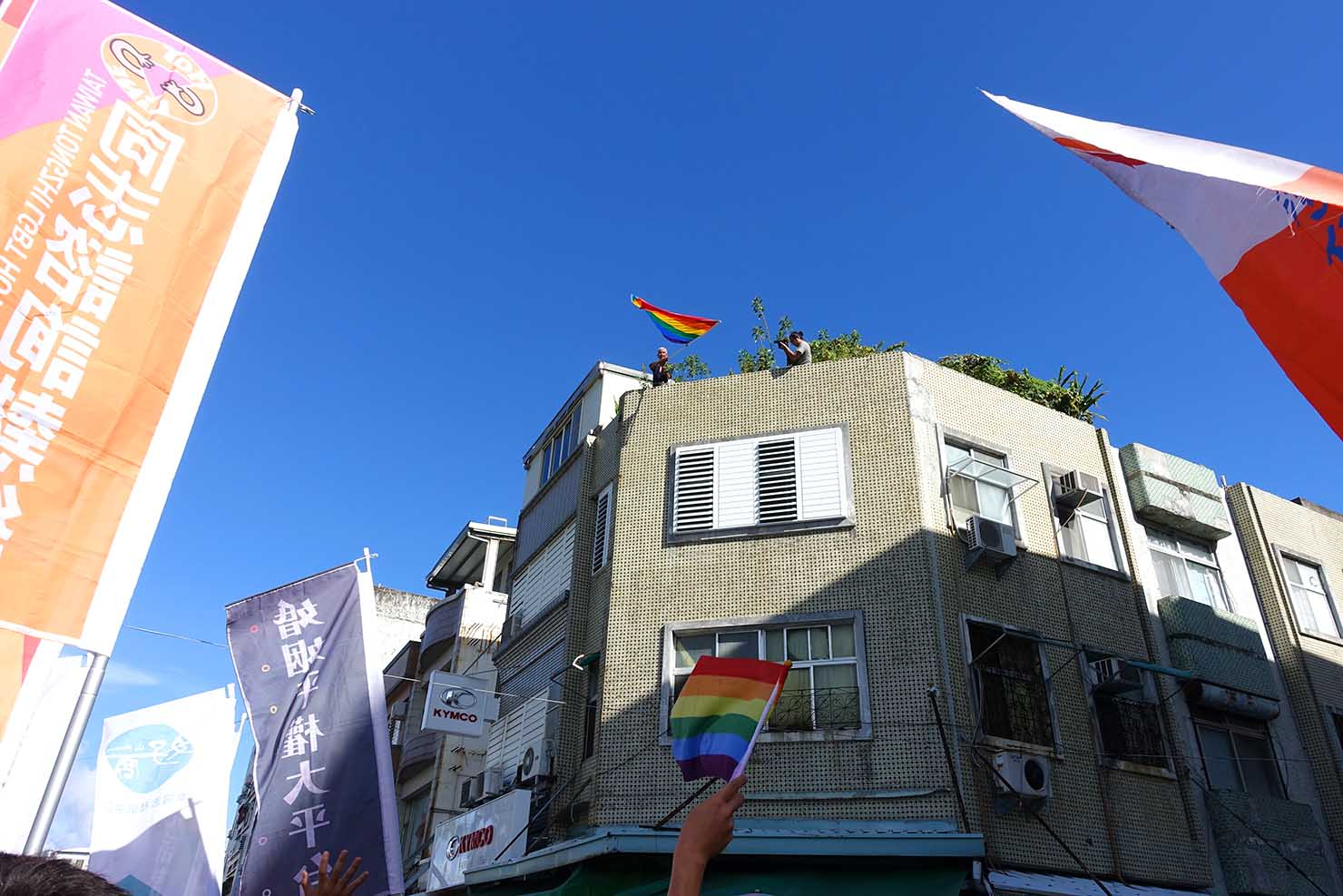台湾東部のLGBTプライド「花東彩虹嘉年華」で屋上からレインボーフラッグを振る活動家・祁家威氏