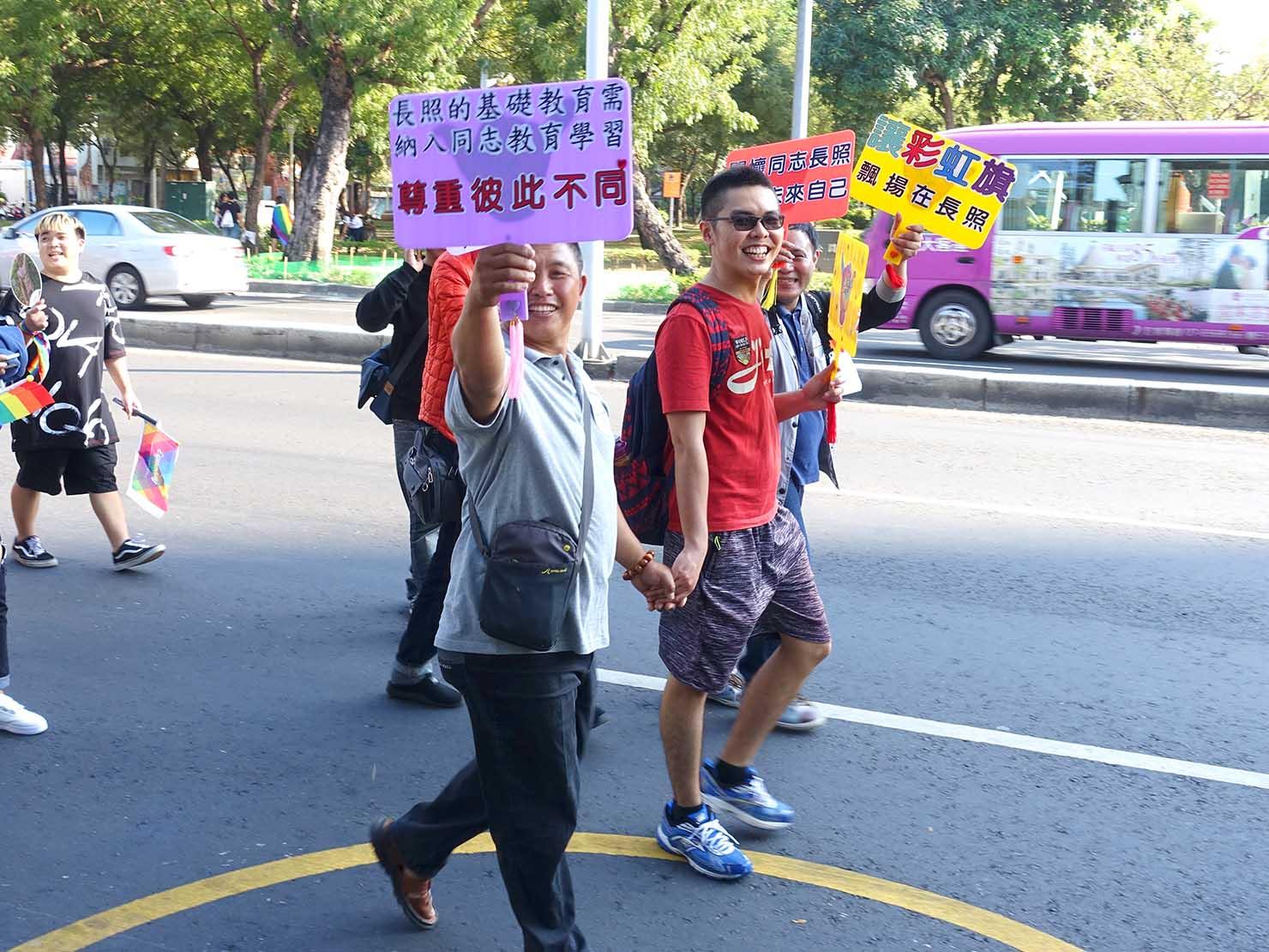 高雄同志大遊行(高雄レインボーパレード)2017で手を繋いでプラカードを掲げるゲイカップル