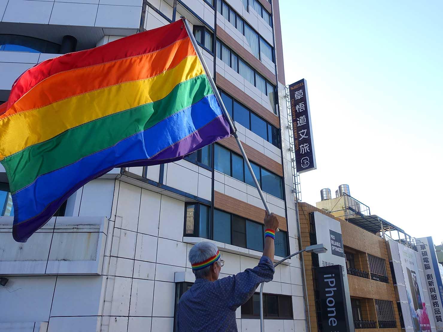 台中同志遊行(台中LGBTプライド)2017の歩道橋からレインボーフラッグを振る活動家・祁家威氏