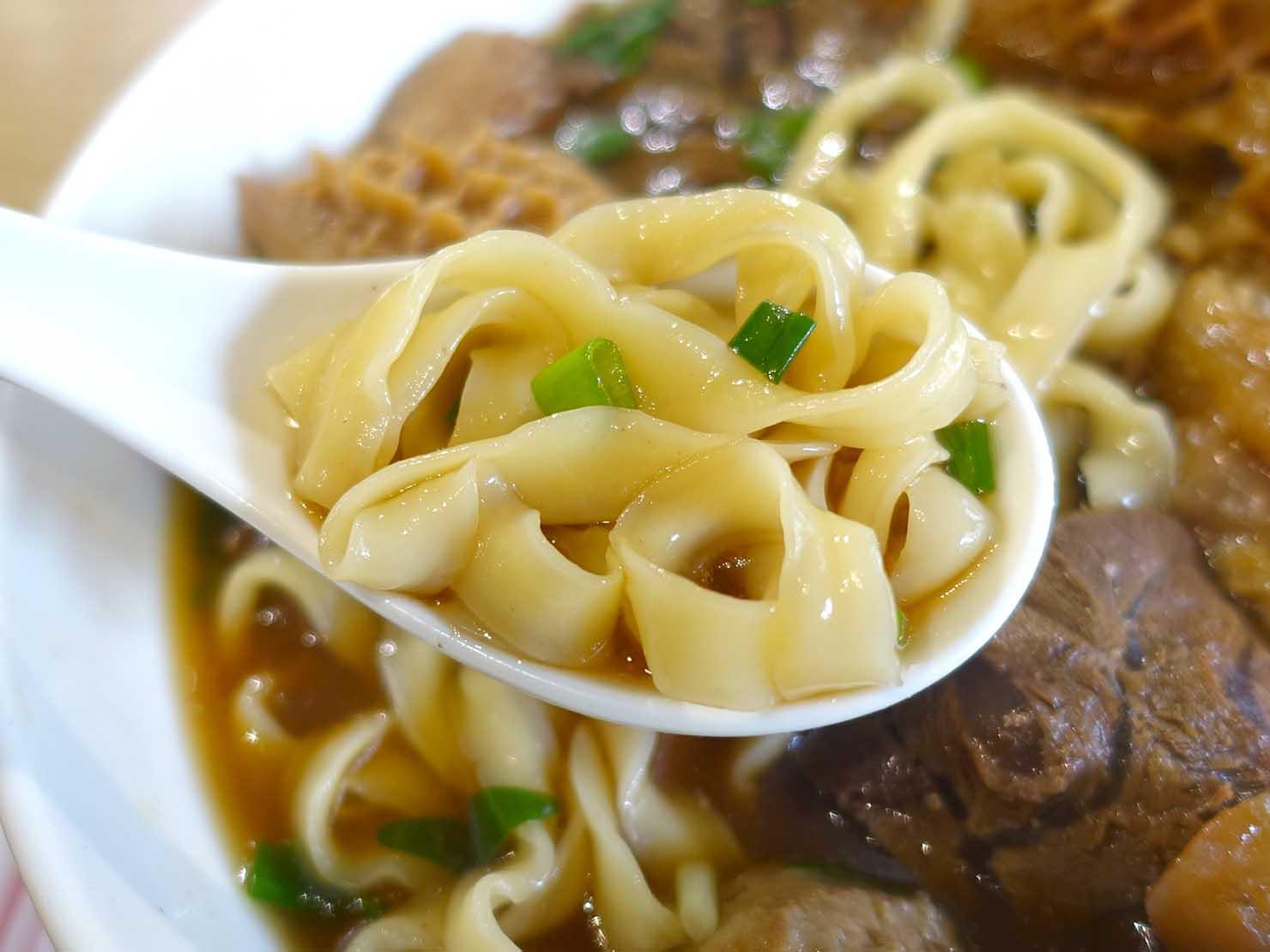 台北の有名牛肉麵店「北芳園」の看板メニュー「添好運六寶牛肉麵」レンゲに入った麺のクローズアップ