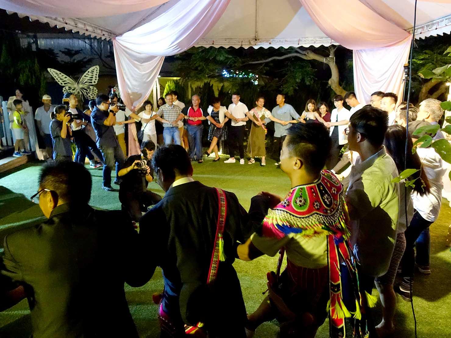 台湾の結婚式で原住民族・阿美族(アミ族)の伝統衣装に身を包んで参列者たちと踊る新郎新婦