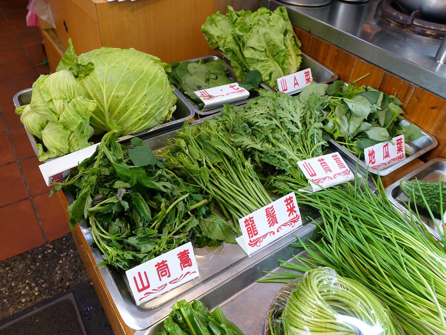 台北・烏來老街グルメ店の軒先に並ぶ山菜
