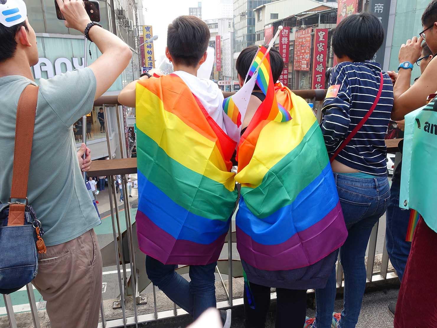 台中同志遊行(台中LGBTプライド)2018のパレードを眺めるレインボーフラッグを纏った参加者