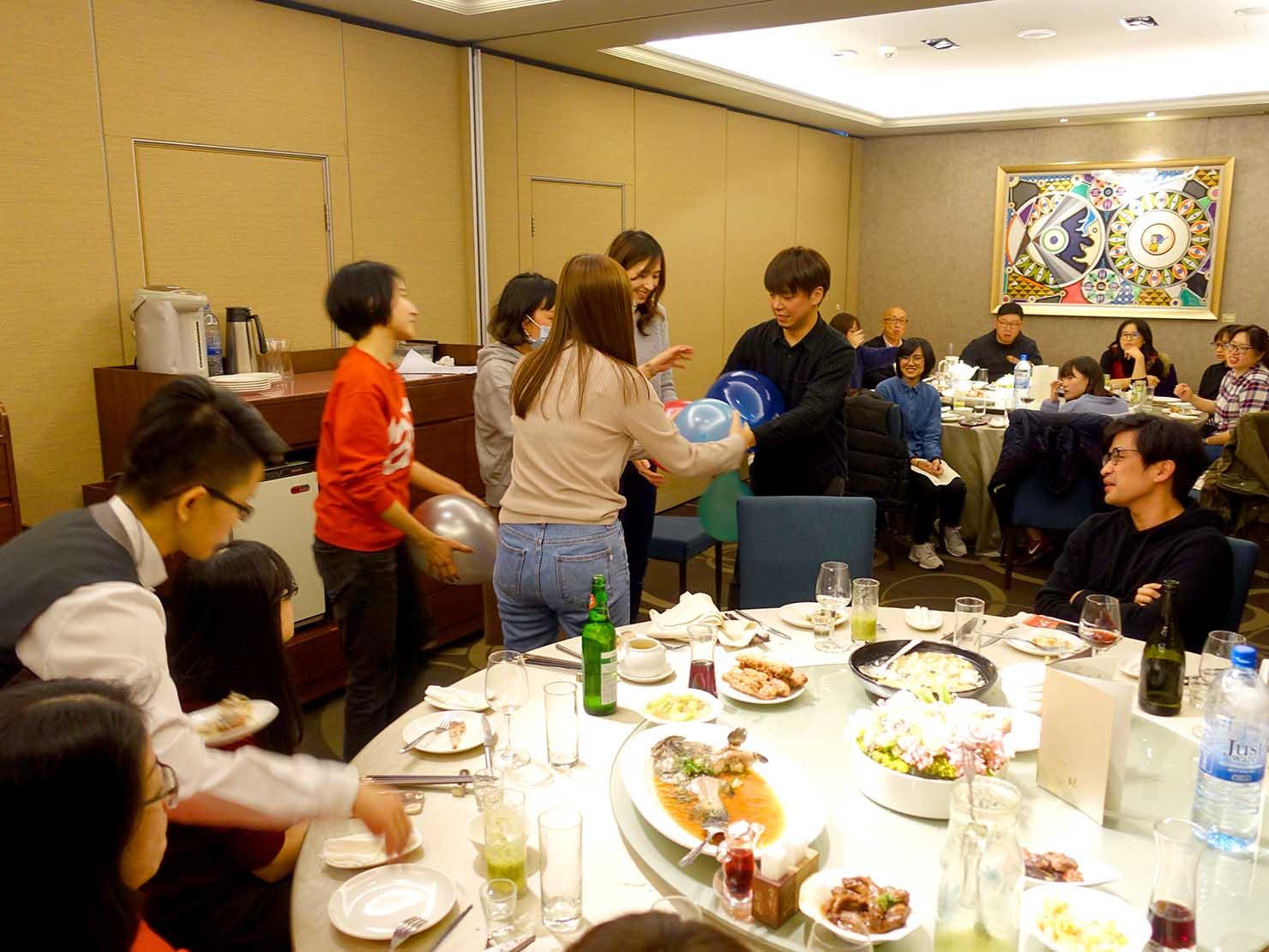 台湾春節前の定番忘年会「尾牙(ウェイヤー)」の紅包争奪ゲームに参加する同僚たち
