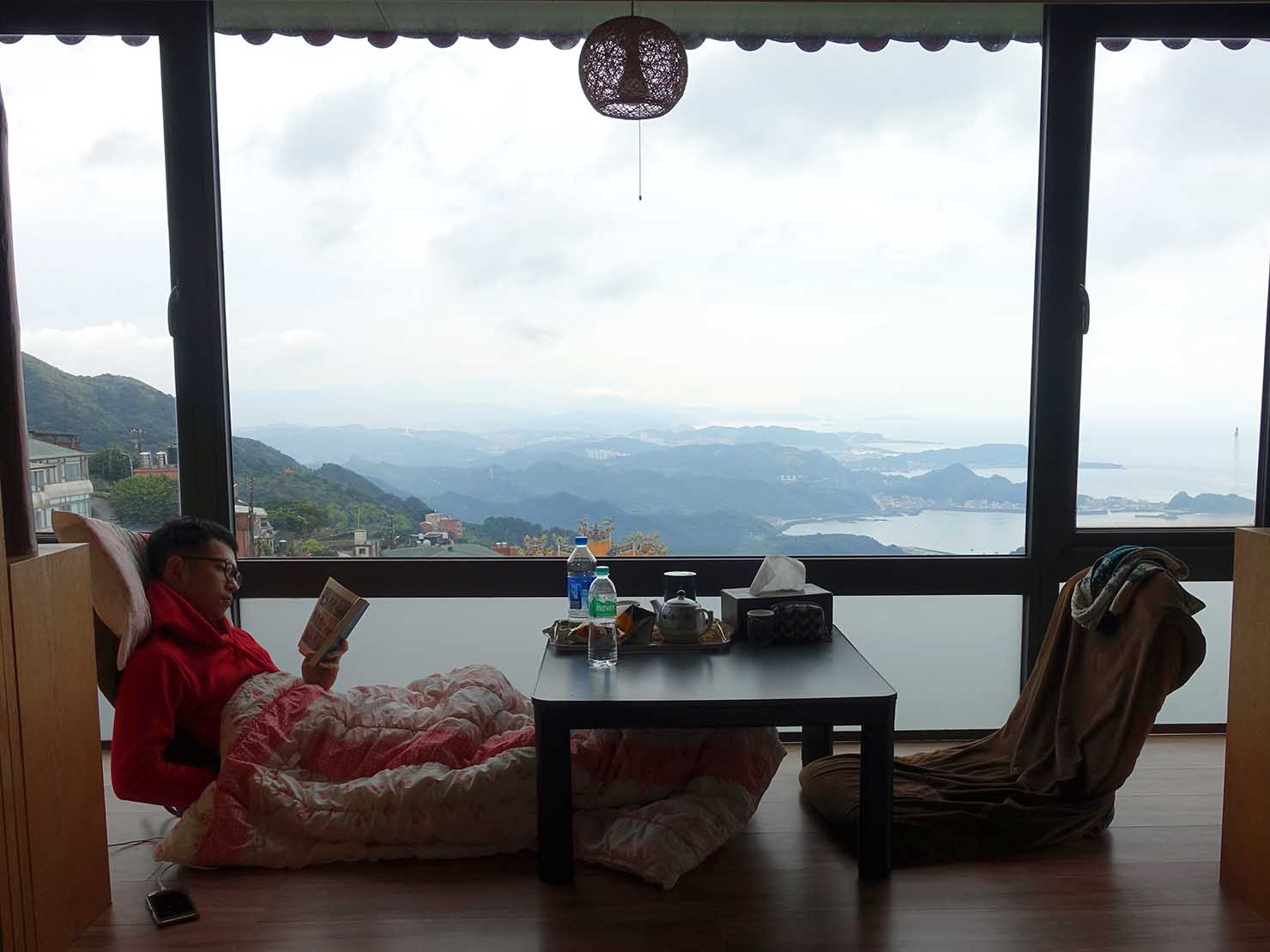 台北・九份のおすすめゲストハウス「九份小町」海景套房(オーシャンビュー・ダブルルーム)の窓辺で読書