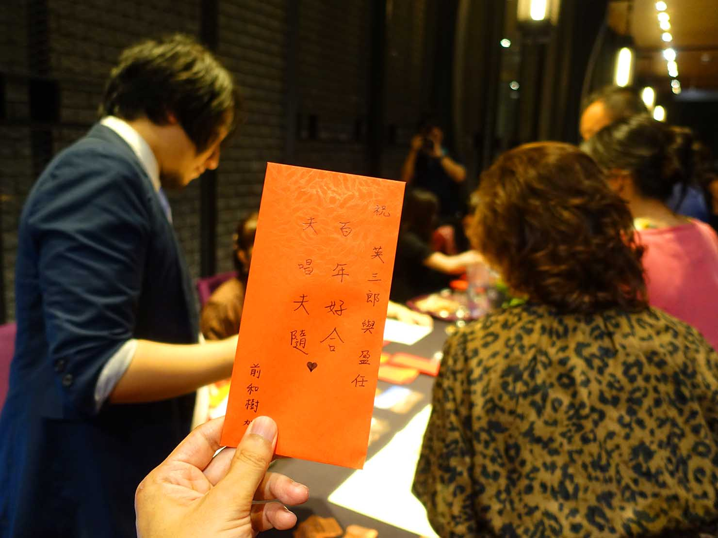 台日同性カップルの友人の結婚式場受付で紅包を渡す