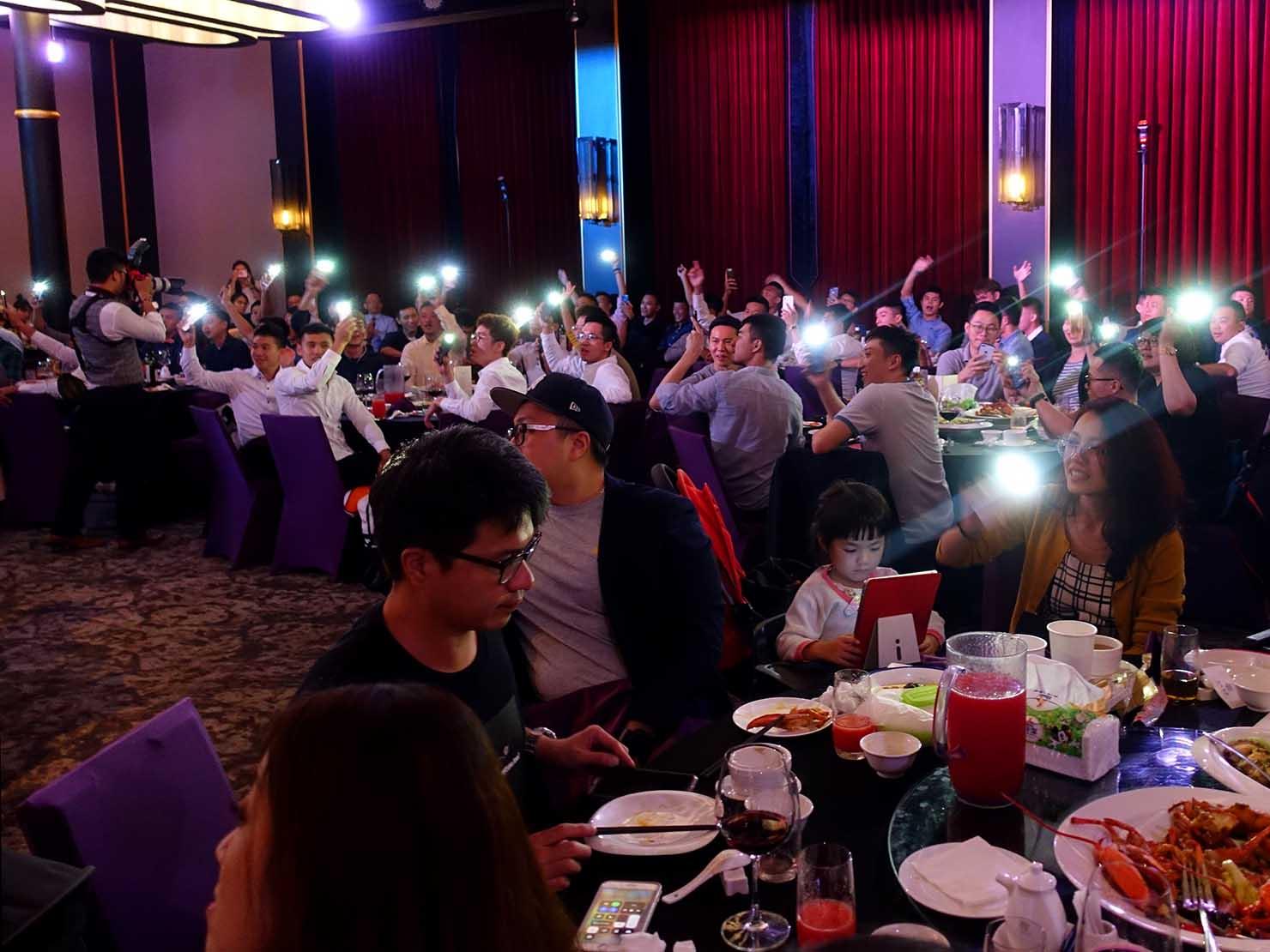 台日同性カップルの友人の結婚式会場でスマホライトをかざす友人たち