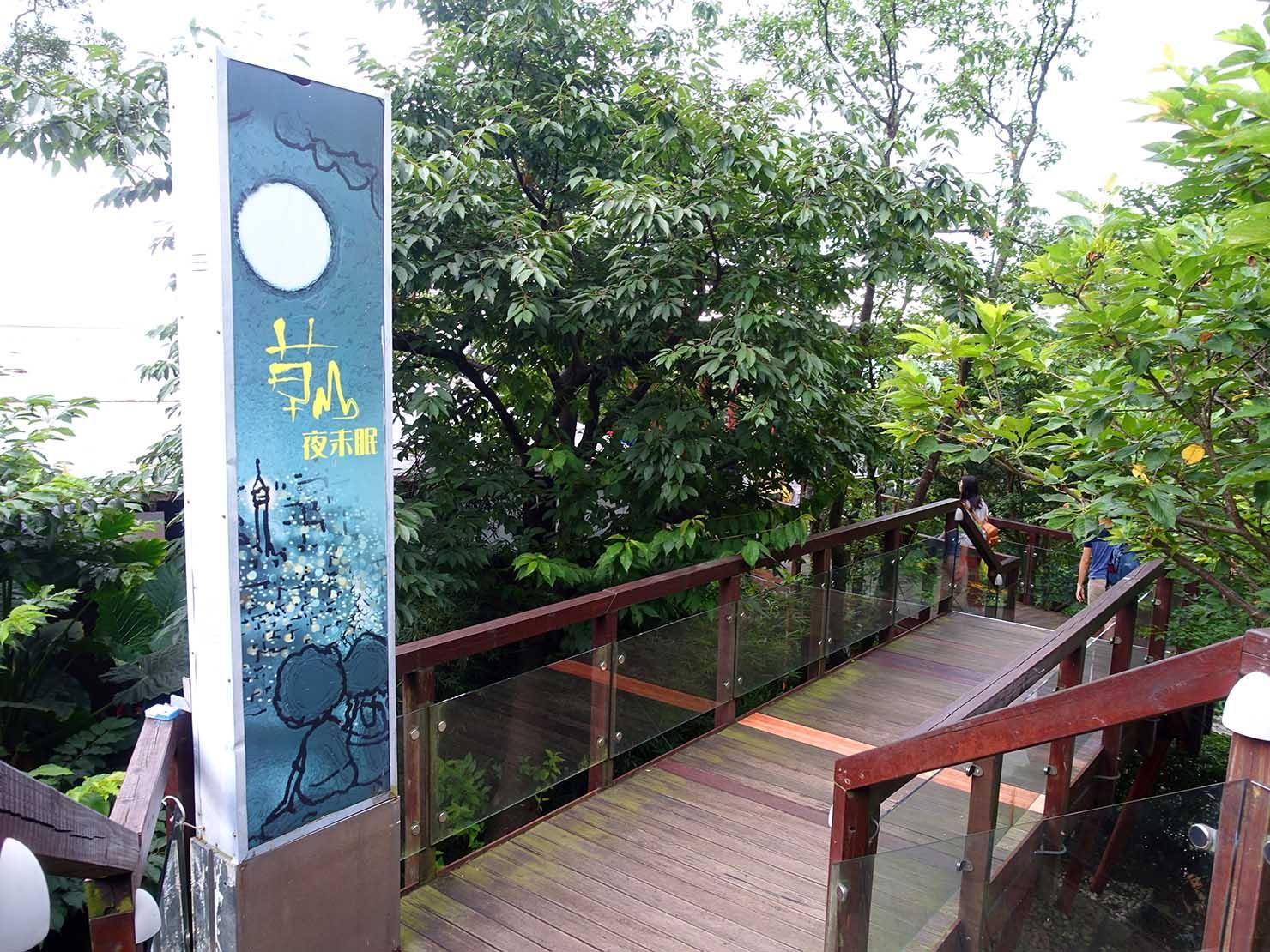 台北・陽明山のレストラン「草山夜未眠」エントランスの木造デッキに立つ看板