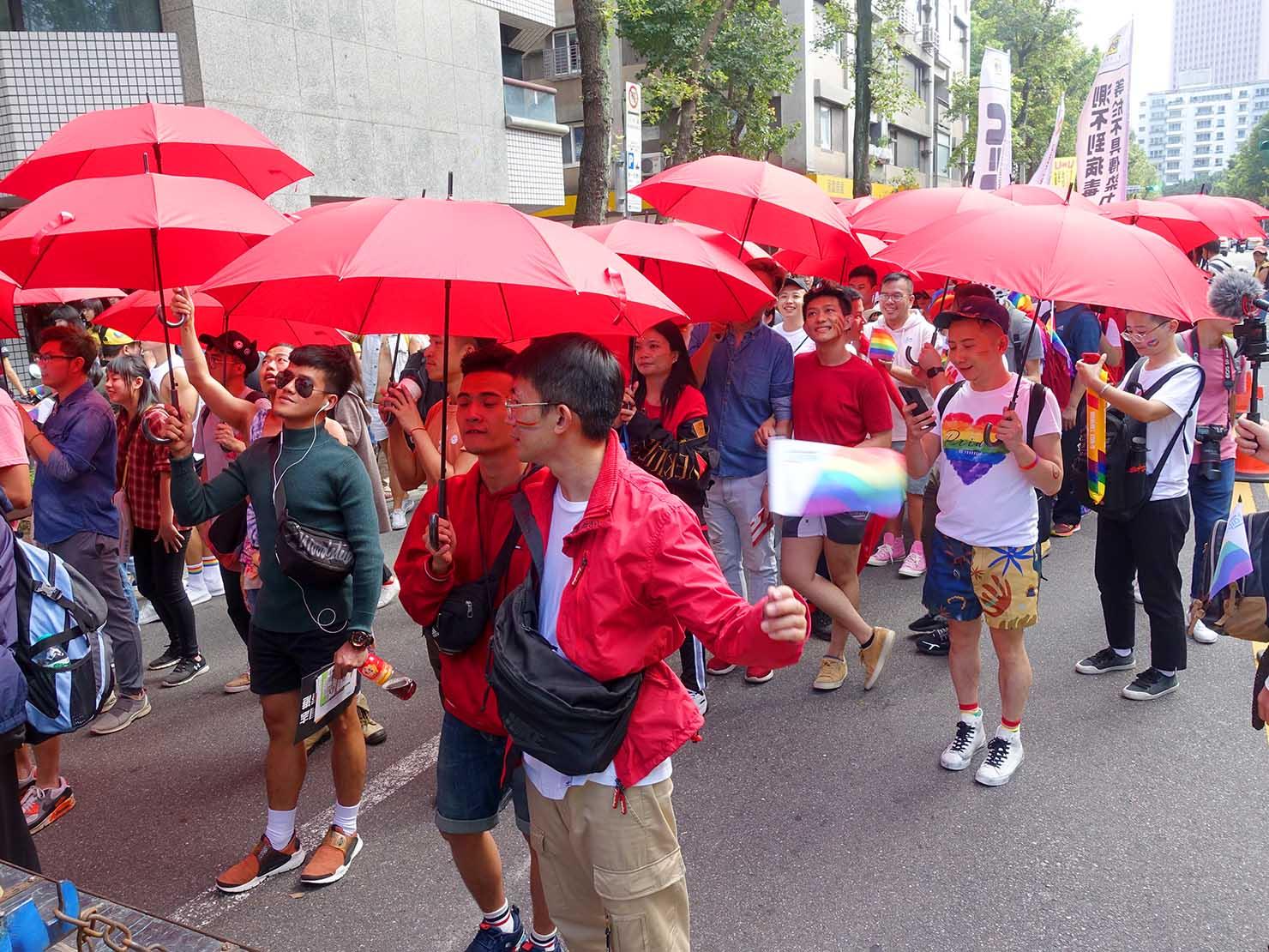 台灣同志遊行(台湾LGBTプライド)2019のパレードを赤い傘をさして歩くグループ
