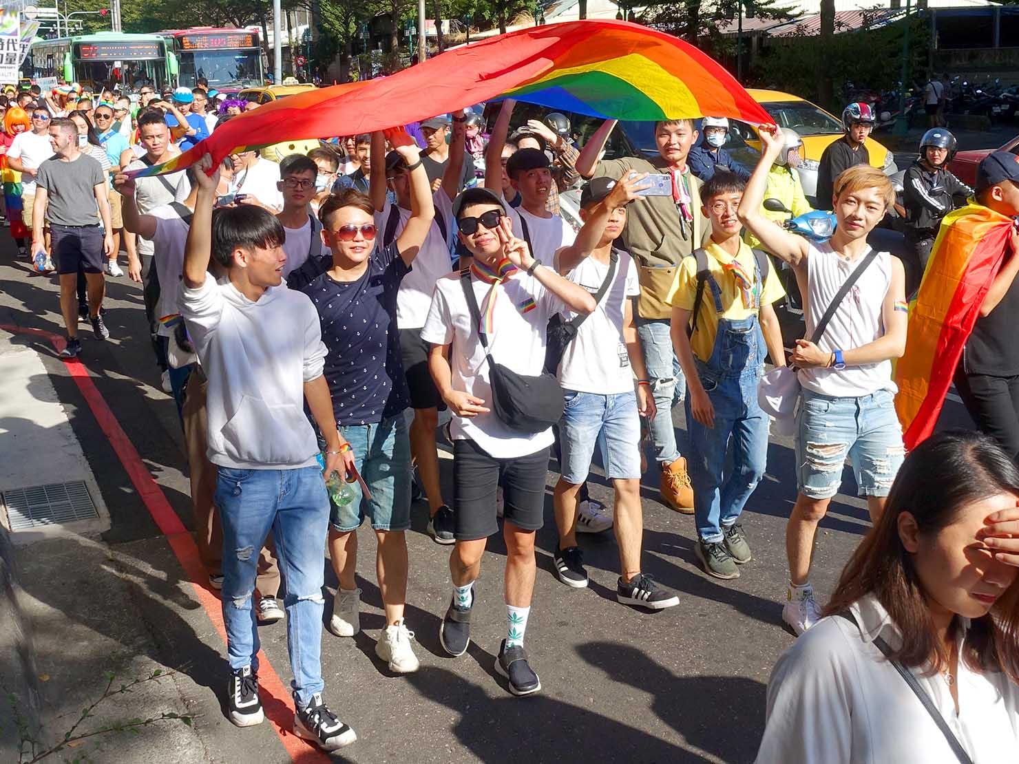 台中同志遊行(台中LGBTプライド)2019のパレードをレインボーフラッグを掲げて歩く参加者たち