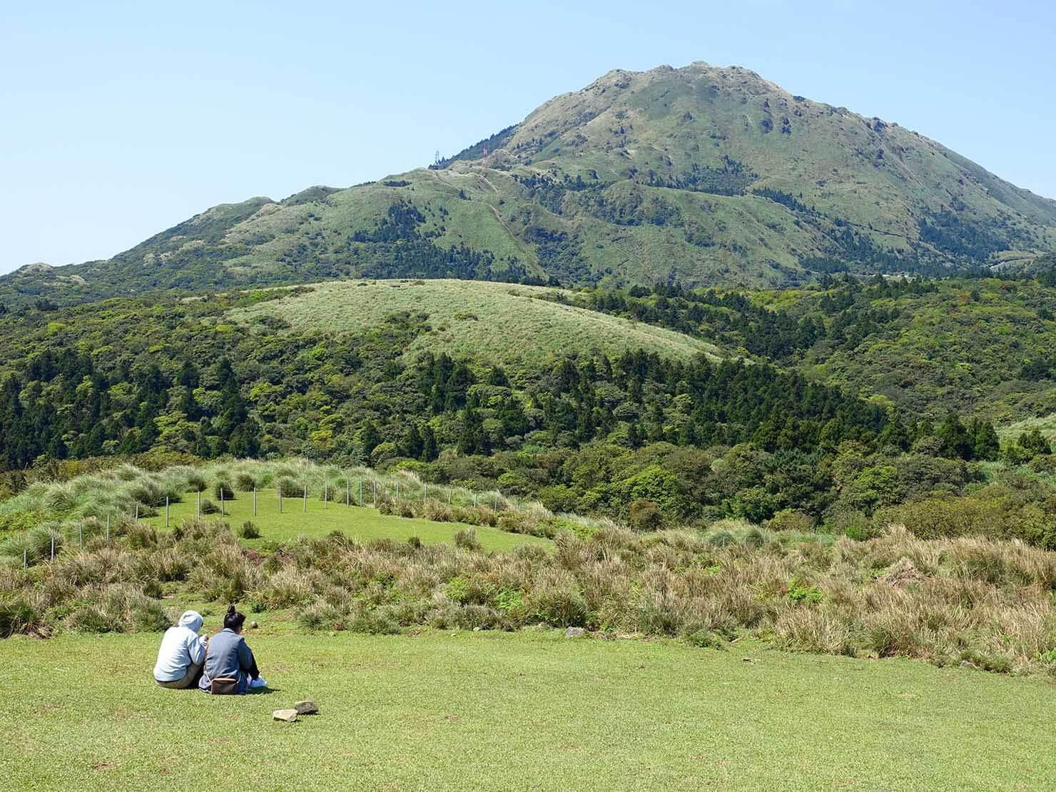台北・陽明山のおすすめスポット「擎天崗」で草原に座るカップル