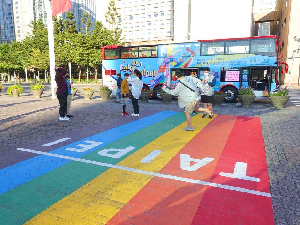 台北のLGBTスポットを巡る観光バス「Color Taipei 彩虹觀光巴士」の第1スポット・台北市政府前のレインボー歩道で記念撮影する参加者