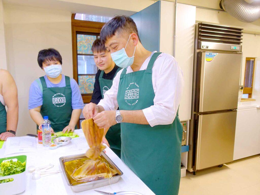 台湾料理教室&プライベートレストラン「好客台北 Be My Guest Taipei」のキッチンでスルメイカの調理方法をレクチャーするオーナーさん
